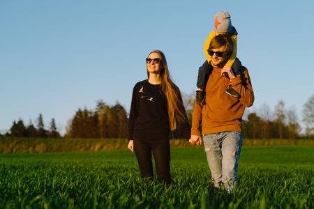 Young parents with a young son walking on a field at sunset in the summer. Concept of family Stock Photo