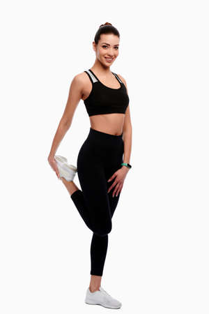 Slim strong athletic woman in sport wear doing stretching exercise in white isolated background