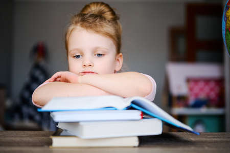 ? ute little schoolgirl is tired of reading books at home at the table and is sad. Girl Does Homework. Distance learning