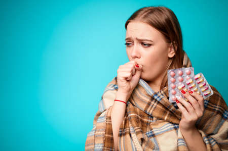 Woman with a virus coughs and holds pills in her hands wrapped in a plaid. Blue background Reklamní fotografie