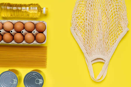 Set of products on yellow background with string bag, flatlay, top view-sunflower oil, chicken eggs, tray, canned, pasta, vermicelli, top view, food, plastic bottle, shop goods