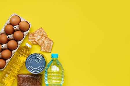 Yellow background with food supplies bread crumbs, biscuits, buckwheat, eggs, plastic bottle of water, canned goods, sunflower oil for the period of quarantine. Copyspace. Flatlay