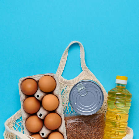Top view, flatlay. Set of products inside string bag on the blue background. Packaging food from the store. Sunflower oil, eggs, canned food, buckwheat. Delivery and donation concept