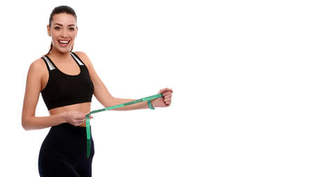 Strong and slim caucasian athletic woman measuring abs on white isolated background
