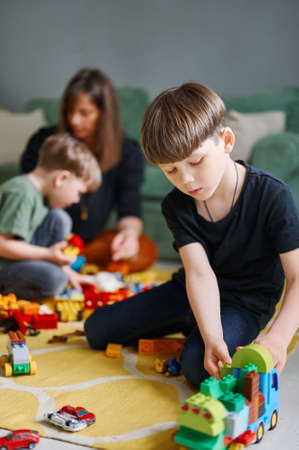 Toddler boy playing with construction blocks at home, mother and brother on the background