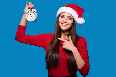 Xmas celebration, new year concept. Smiling woman wearing red santa hat point finger to clocks, isolated blue background