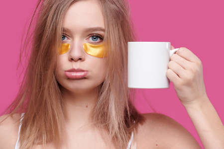 Tired and drunk woman with hangover put patches on the eyes holding white cup of coffee