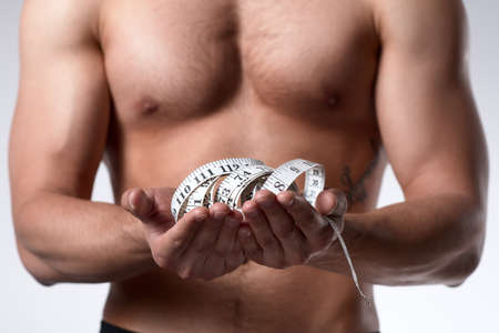 Muscular man is being measured. Strong man with muscular body holds white measuring tape on his hands. Isolated on white background