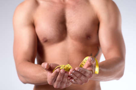 Muscular man is being measured. Strong man with muscular body holds yellow measuring tape on his hands. Isolated on white background