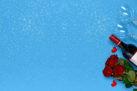 Wine bottle, roses and wine glasses with snowflakes on blue background top view with place to insert text. Valentines day concept