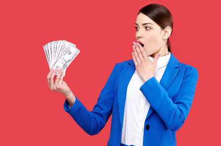 Excited business woman holding dollar banknotes and close mouth with palm in red isolated background, bet or casino concept