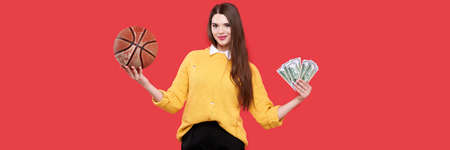 Bet, lottery and casino concept. Young smiling woman holding basketball ball and bunch of dollars happy smiling on red background