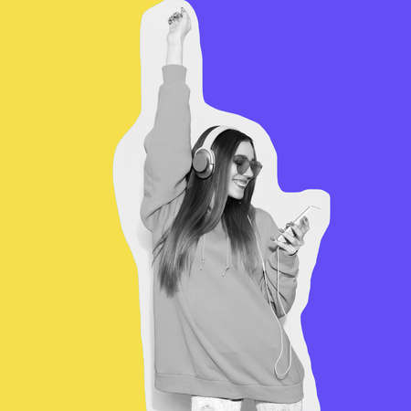 Enjoy life. Laughing hipster girl wearing trendy oversize hoodie listening to music on her headphones on colored background