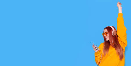 Smiling girl listen music on headphones and holding smartphone on blue background 写真素材