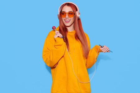 Hipster teenage girl wearing trendy oversize hoodie eats lollipop and listen to music in headphones on blue background