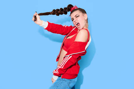 Young hipster teenage girl in bright casual retro clothes and long hair have fun on blue background 写真素材