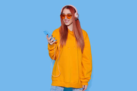 Young female in oversize hoodie listening to music on headphones and holding smartphone on bright blue background