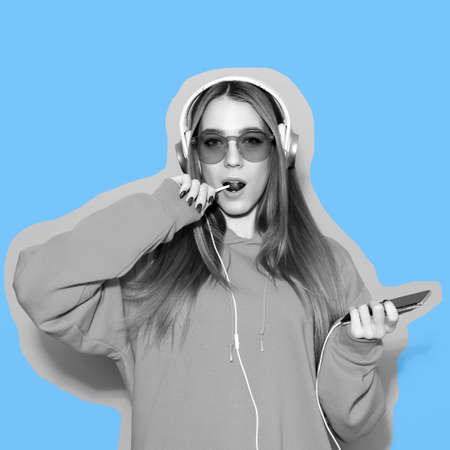 Magazine style collage. Girl in headphones eat lollipop and listen to music on blue background