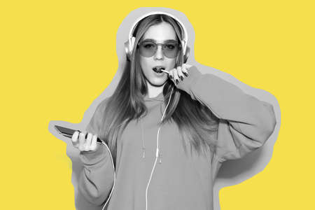 Sexy girl wearing hoodie listen to music in headphones and lick lollipop on yellow background