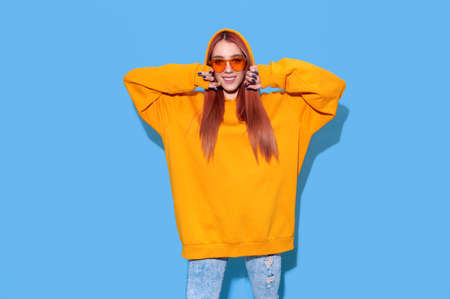 Teenage hipster girl in orange oversize hoodie and trendy sunglasses on bright blue background 写真素材