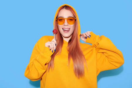 Attractive hipster girl wearing hoodie lick lollipop and show tongue on blue background