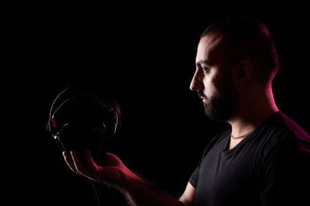 Young bearded Arab DJ musician holds headphones in his hands. International DJ Day Stock fotó