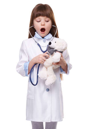 Doctor girl in white medical coat listens to heartbeats with stethoscope at toy bear on white isolated background