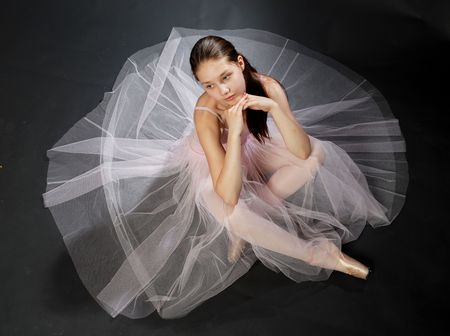 Young ballerina in rose dress sitting on the floor