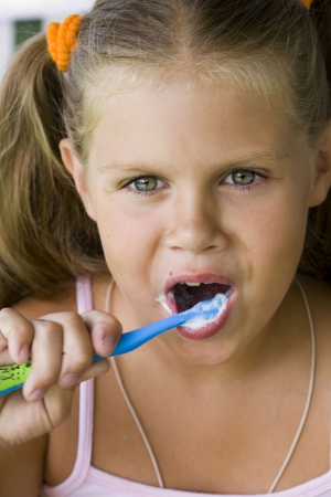 little blond girl cleaning teeth by toothbrush