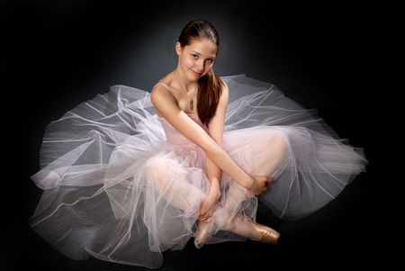 ballet: Young ballerina in rose dress sitting on the floor