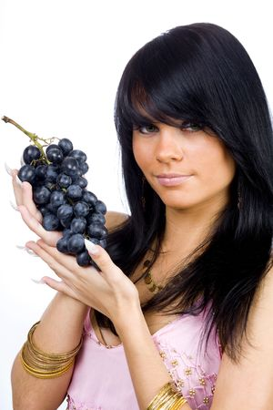 young long hair brunette with bunch of black grapes