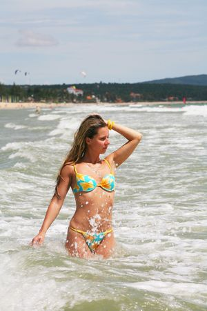 Young blonde woman walking in water of an ocean Stock Photo - 3868716