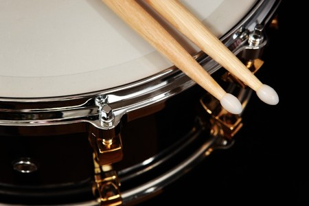 tambores: cerca de tambor con baquetas sobre fondo negro Foto de archivo