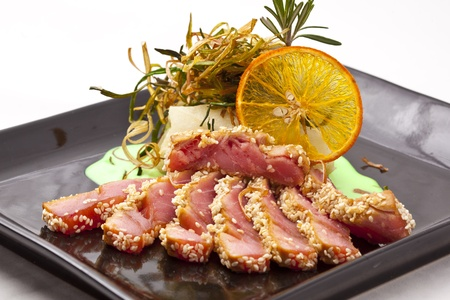 pieces of tuna with sesame  and green sause on black plate  Stock Photo