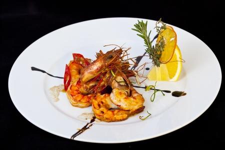 Roasted srimps with orange on white plate