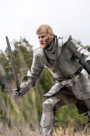 Knight with sword defending himself in forest