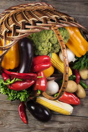 Photography of different vegetables on wooden table in basket. Healthy food background.