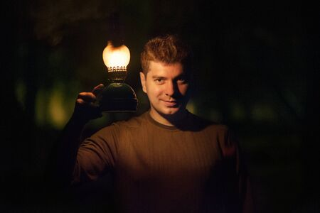 Young man with a burning lamp ooking into camera.