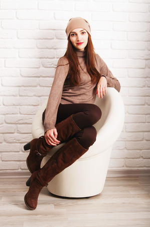 Young beautiful girl in a cap with straight long hair sitting in a round white chair against a white brick wall