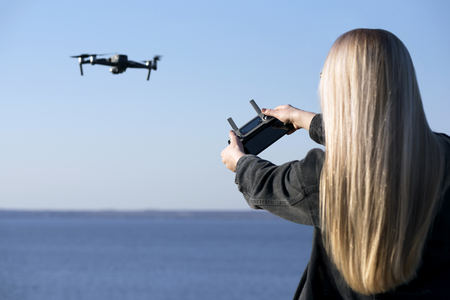 The girl controls the drone on a background of blue sky