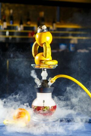 Hookah with a round transparent flask in which there is a red liquid. Hookah bowl of oranges and bananas. Lots of smoke. Black background. Yellow mouthpiece.