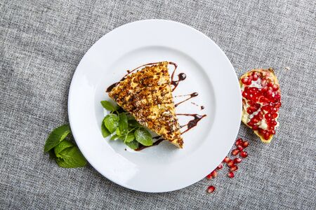 Piece Of Cake Ideal. Dessert. Served on a white plate with a litre of mint.  Near the plate lies a pomegranate and mint leaves. Background-gray canvas. Stok Fotoğraf
