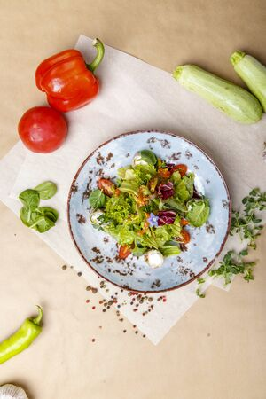 Salmon salad. Plate on a background of gray and white wrapping paper. Around the plate are spread sweet peppers, garlic and onions and zucchini Reklamní fotografie