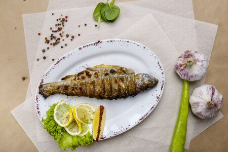 grilled trout with lemon and lettuce on a white plate. The plate is on white and gray wrapping paper, lined with pepper, peas, tomatoes, garlic, herbs
