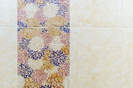 Square ceramic tiles in the form of blue, yellow, red and white leaf patterns on the wall in the bathroom. White-yellow patterns alternate with colored ones