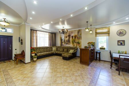 large room with sofa and table in classic style. Large leather sofa, cherry wood wine rack, dining table. Light tiles on the floor.