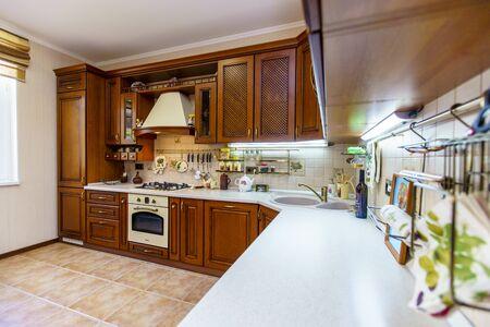 Warme und einladende Küche mit großer Kücheninsel, Kirschholzschränken, goldenen Granitarbeitsplatten und modernem Edelstahlkühlschrank. Moderne Küche im Luxushaus.