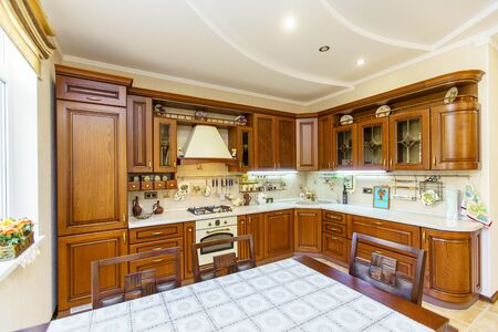 Warm and inviting kitchen with large kitchen island, cherrywood cabinets, gold granite counter tops and modern stainless steel refrigerator. Modern kitchen in luxury house. Stock Photo