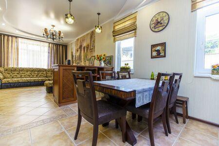 grande chambre avec canapé et table de style classique. Grand canapé en cuir, casier à vin en merisier, table à manger. Carrelage clair au sol.
