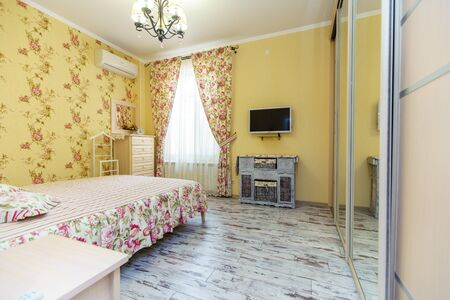 An elegant bedroom in the Provence style. Bright Wallpaper and curtains in floral patterns. White bed with light floral bedspread. The floors in the style of Provence